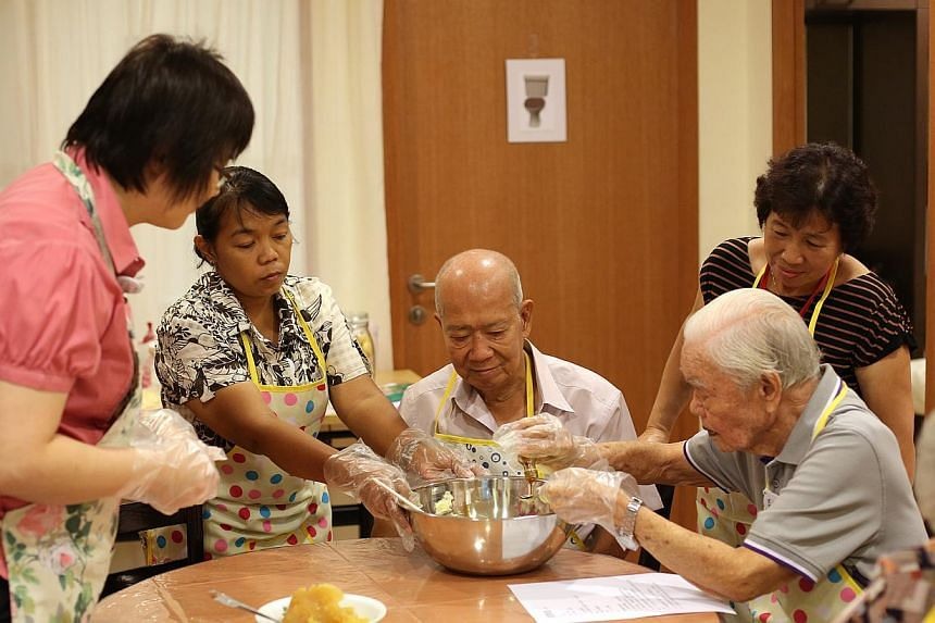 Dementia clients and their caregivers making pineapple tarts as part of a cooking therapy class in a mock-up kitchen at ADA's training centre in Bendeemer Road. Cooking is used as a tool to bond and jog memories.