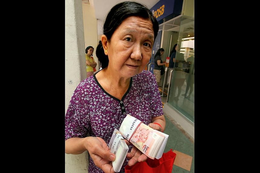 A long line of customers outside a POSB branch in Bedok yesterday morning. Among the early birds was Ms Woo Seoon Lee (above), 67, who started queueing even before the branch opened. -- ST PHOTOS: LAU FOOK KONG