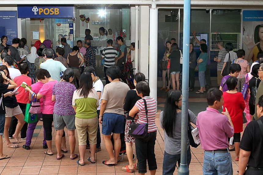 A long line of customers (above) outside a POSB branch in Bedok yesterday morning. Among the early birds was Ms Woo Seoon Lee (left), 67,  who started queueing even before the branch opened.