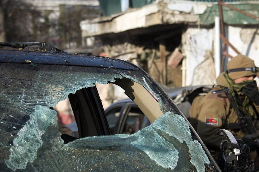 An Afghan special force soldier passes a damaged car next to the entrance of a Lebanese restaurant that was attacked in Kabul, on Jan 18, 2014. Survivors of the Taliban suicide attack on a restaurant in Kabul told on Saturday of the carnage and blood