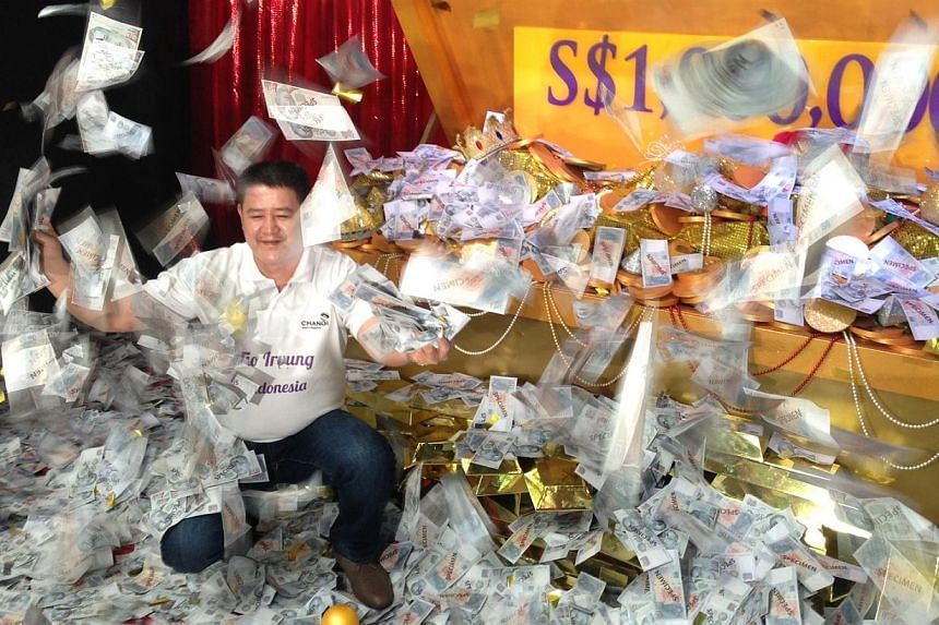 """Indonesian businessman Irvung Tio became a million dollars richer on Sunday, after he became the latest lucky winner of Changi Airport's """"Be a Changi Millionaire"""" draw. -- ST PHOTO: ROYSTON SIM"""