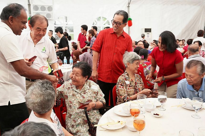 Mr K. Shanmugam (left) gives a hongbao to a senior citizenat a Chong Pang community event on Sunday, Jan 19, 2014, to usher in the Chinese New Year of the Horse. -- PHOTO: ZAO BAO