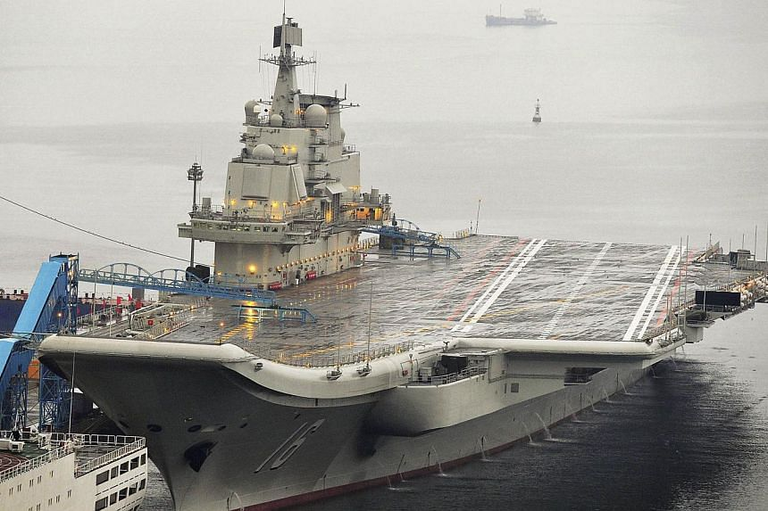China's first aircraft carrier, which was renovated from an old aircraft carrier that China bought from Ukraine in 1998, is seen docked at Dalian Port, in Dalian, Liaoning province in this September 22, 2012 file photo. -- FILE PHOTO: REUTERS
