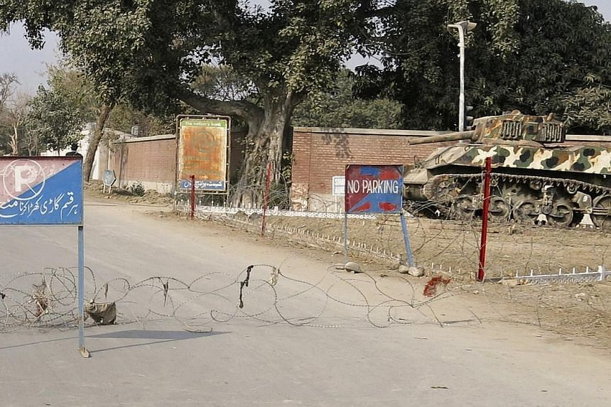Barbed wire, placed by security officials, cordons off a road leading towards the site of a bomb blast in Bannu January 19, 2014. At least 20 Pakistani soldiers were killed on Sunday when an explosion hit an army convoy in the northwestern town Bannu