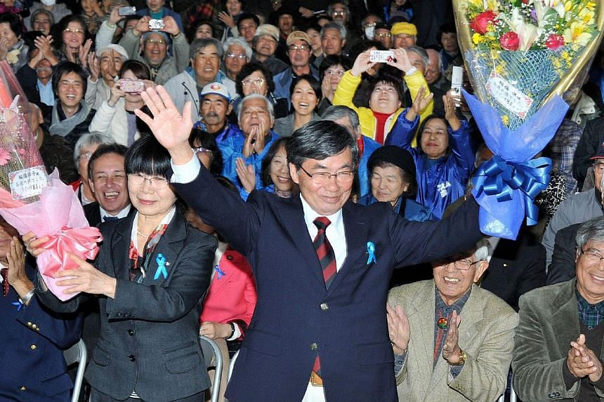 Mr Susumu Inamine (front, centre), a candidate for mayoral election in Nago, celebrates his victory with supporters on January 19, 2014. Mr Inamine won in a mayoral election on the southern Japanese island of Okinawa which is being closely watched as