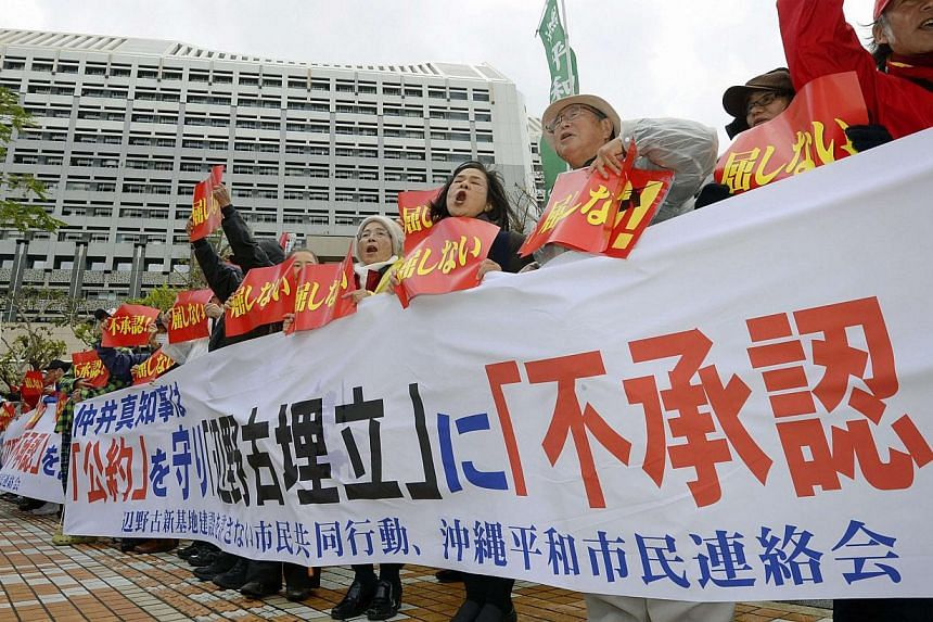 Protesters shouting slogans during a rally against the relocation of a US military base in front of the Okinawa prefectural government office building in Naha on the Japanese southern island of Okinawa, in this photo taken by Kyodo on December 27, 20
