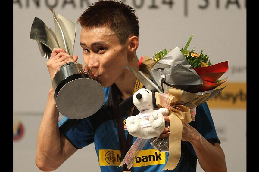 Lee Chong Wei of Malaysia kisses the trophy on the podium after winning the men's singles final match against Tommy Sugiarto of Indonesia during their Malaysia Open Badminton Superseries in Kuala Lumpur on Jan 19, 2014. -- PHOTO: AFP