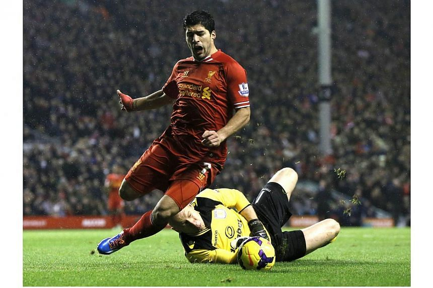 Liverpool's Luis Suarez (left) is fouled by Aston Villa goalkeeper Brad Guzan during their English Premier League soccer match at Anfield in Liverpool, northern England on Jan 18, 2014. Liverpool's Premier League title bid suffered a blow after they