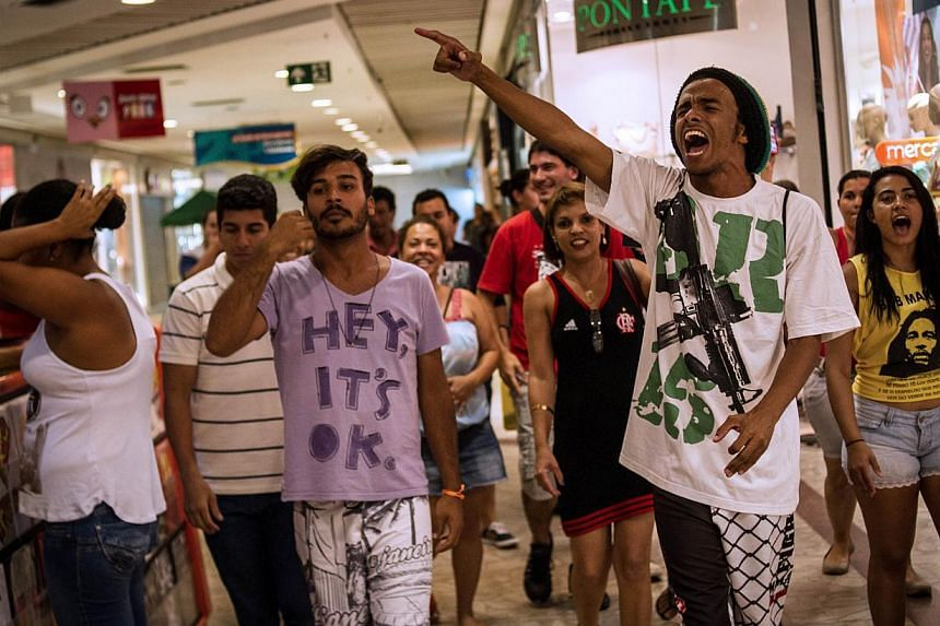 """A group of young people pulling off a """"rolezinho"""" gathering at the Plaza shopping mall in Niteroi, suburb of Rio de Janeiro, Brazil on Jan 18, 2014. Flash mobs of slum teenagers in Brazil's upscale shopping malls are spreading, and stirring black act"""