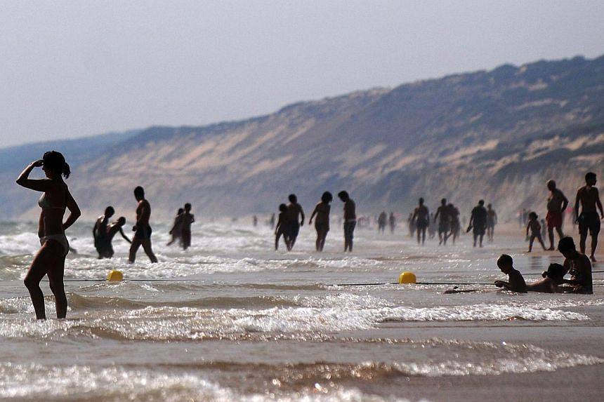 A file picture taken on June 30, 2011 shows people bathing on a beach in southern Spain. -- PHOTO: AFP