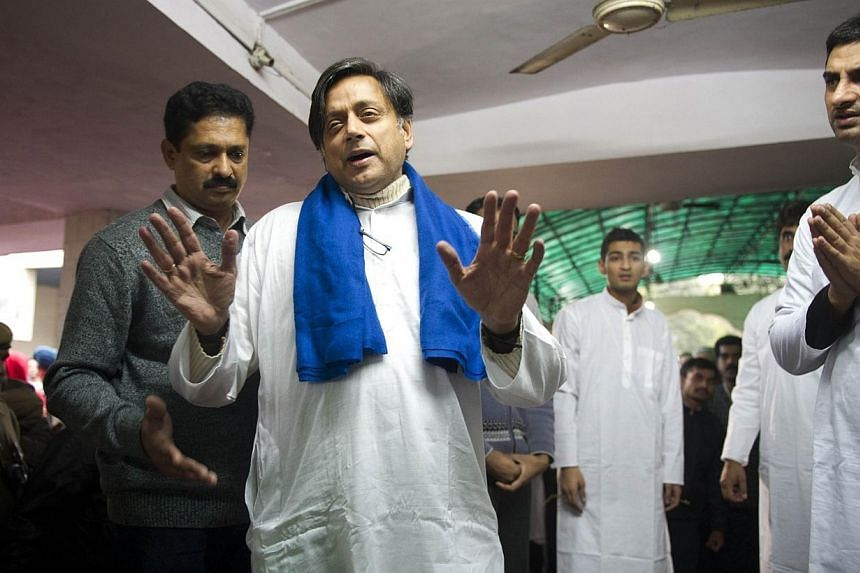 India's Human Resources Minister Shashi Tharoor (centre) gestures to media while escorting the body of his wife Sunanda Pushkar at a cremation centre in New Delhi on Jan 18, 2014.Mr Tharoor, whose wife was found dead in a luxury hotel room, cal
