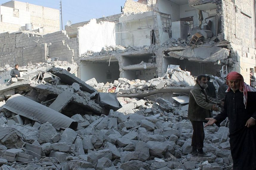 Syrian civilians stand on a damaged street after government forces allegedly shelled the northern Syrian city of Aleppo on Jan 18, 2014. Syria's deeply divided opposition finally agreed on Saturday, Jan 18, 2014, to join an international peace confer