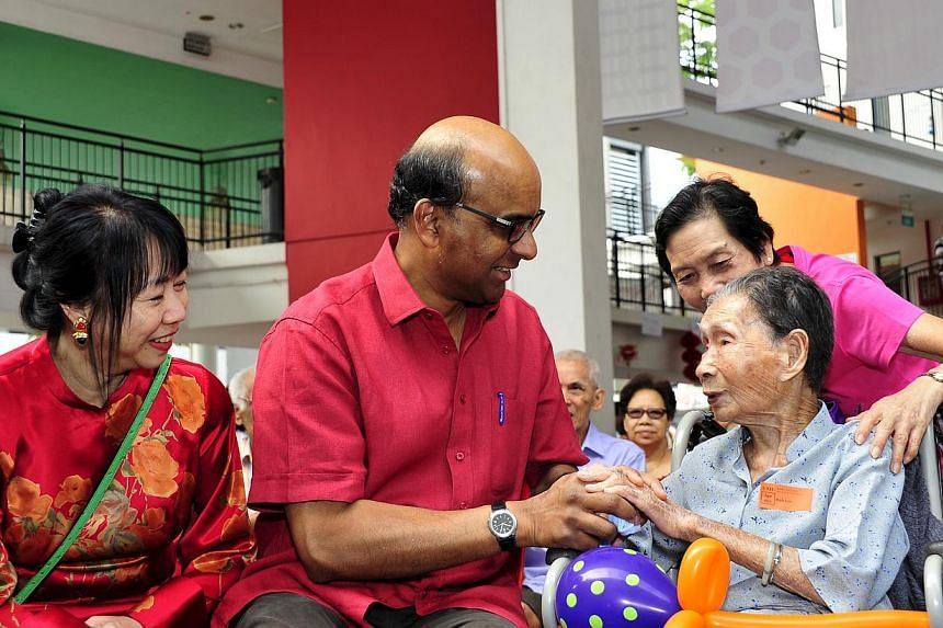 Deputy Prime Minister Tharman Shanmugaratnam (centre) and his wife (left) having a chat with Madam Koh Lee, who is 101 years old, on Sunday, Jan 19, 2014. About 140,000 people have automatically come on board the Community Health Assistance