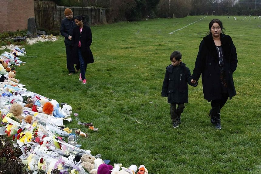 Floral tributes and soft toys left near the home of three-year-old Mikaeel Kular, in Edinburgh, Scotland on Jan 18, 2014. Mikaeel's mother was charged late Saturday in connection with his death, media reports said. -- PHOTO: REUTERS