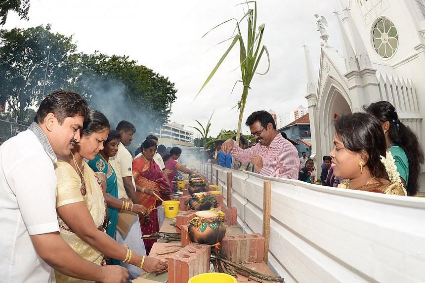 Technical officer Arul Selvam (above, left), 34, and staff nurse A. Amala Praba, 30, both from Chennai, watching as pots of pongal or special sweet rice are being prepared while others make traditional decorations in the compound of the Church of Our