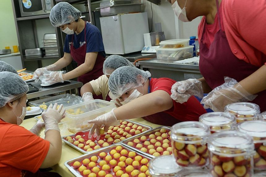 Minds trainee Alvin Teo (centre), 28, with other trainees at SIA-Minds Employment Development Centre, making pineapple tarts for sale during the Chinese New Year season. Minds runs five social enterprise programmes. -- ST PHOTO: NG SOR LUAN