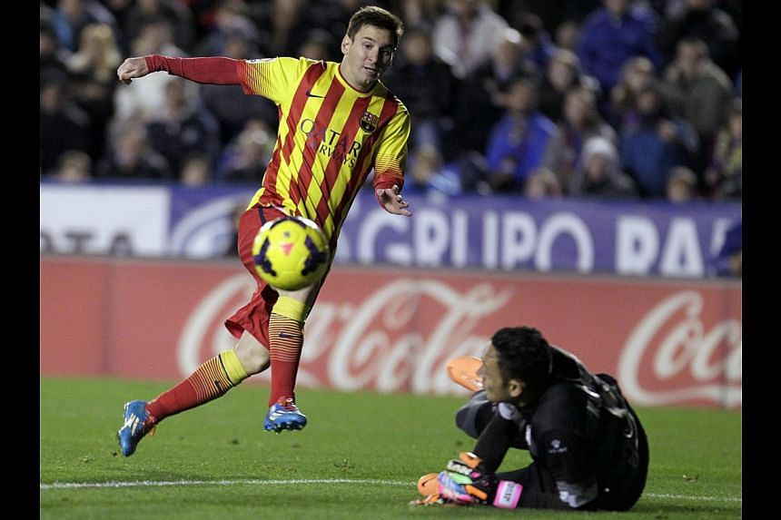 Barcelona's Lionel Messi (left) kicks the ball next to Levante's goalkeeper Keylor Navas during the match at the Ciudad de Valencia stadium in Valencia on Jan 19, 2014. Messi's first league start of 2014 could not inspire Barcelona to victory as the