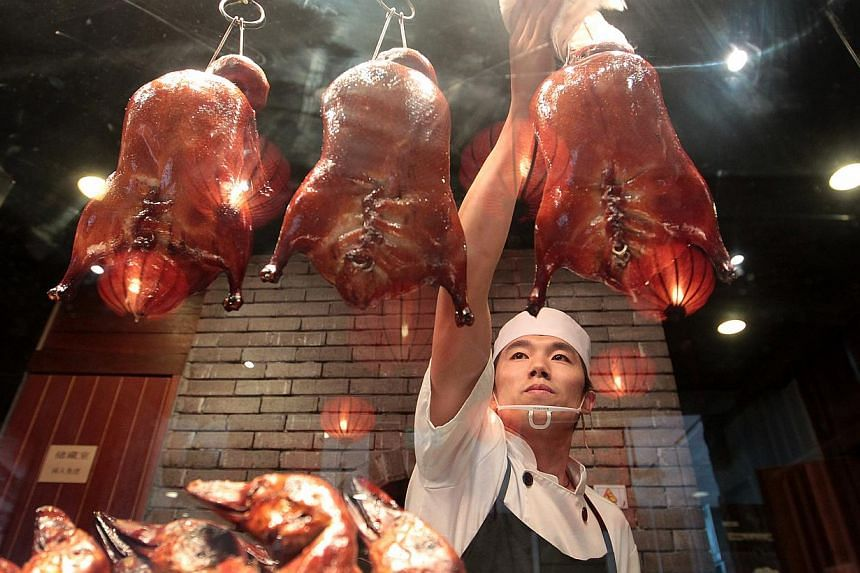 Dian Xiao Er's duck chef Li Xue Liang, 27, removes the herbal roasted ducks from the over and displays them at the shop window.If youregularly order goose at Chinese restaurants, you may have noticed a difference in the way it tastes thes