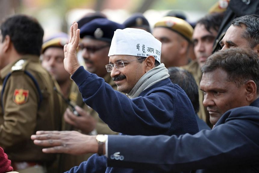 New Delhi Chief Minister Arvind Kejriwal waves to supporters as he sits during a protest in the streets of New Delhi on Jan 20, 2014. The campaigning chief minister of New Delhi who swept to power last month after leading protests against corruption