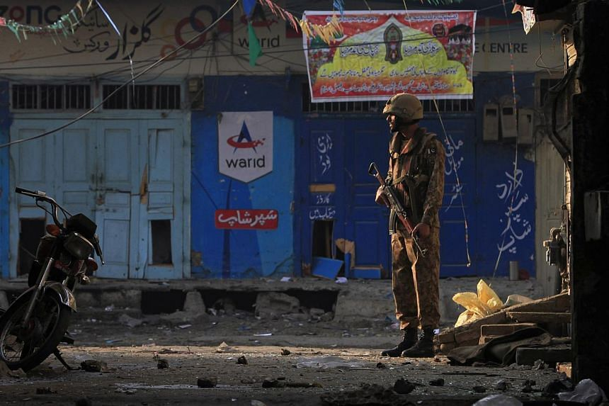 A Pakistani soldier stands guard near the site of a suicide blast in Rawalpini, on Jan 20, 2014. A Taleban suicide bomber killed at least 13 people in a market next to Pakistan's military headquarters on Monday, a day after one of the deadliest attac