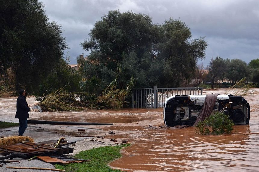 A man watches an overturned car near the Maravenne river on Jan 19, 2014 in Londe-les-Maures after floods struck southeastern France.One man died on Sunday and more than 150 people had to be airlifted to safety after floods struck south-eastern