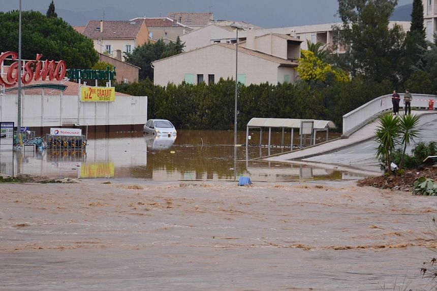 Residents (right) watch a flooded Casino hypermarket store near the Pansard river on Jan 19, 2014 in Londe-les-Maures after floods struck south-eastern France. -- PHOTO: AFP