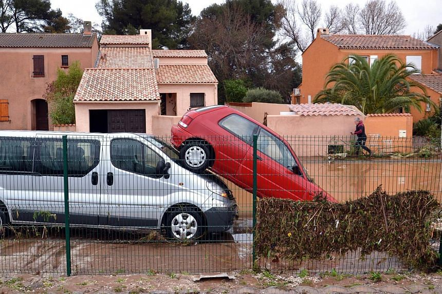 A picture taken on Jan 19, 2014, shows a car parked on top of another in a residential area near the Pansard river in Londe-les-Maures after floods struck south-eastern France. -- PHOTO: AFP