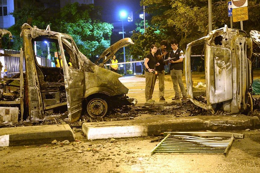 Police officers examining an ambulance and a police car that were burnt beyond recognition along Race Course Road at the aftermath of the Little India riot in Dec 8, 2013.A new bill introduced in Parliament on Monday, Jan 20, 2014, will give po