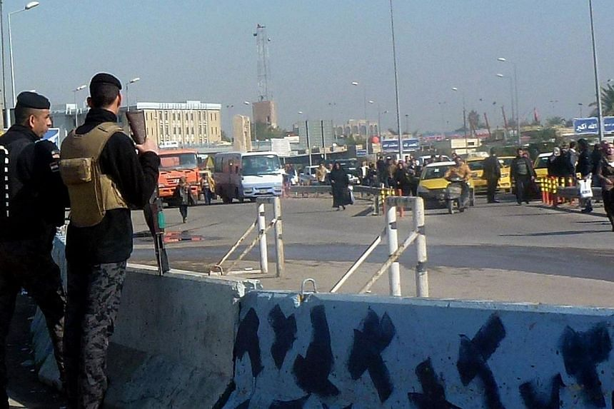Iraqi police cut off a road leading to a taxi and bus station in the Allawi area of the capital Baghdad where a car bomb targeting army recruits exploded on Jan 12, 2014.Seven bomb explosions killed 26 people and wounded 67 in the Iraqi capital
