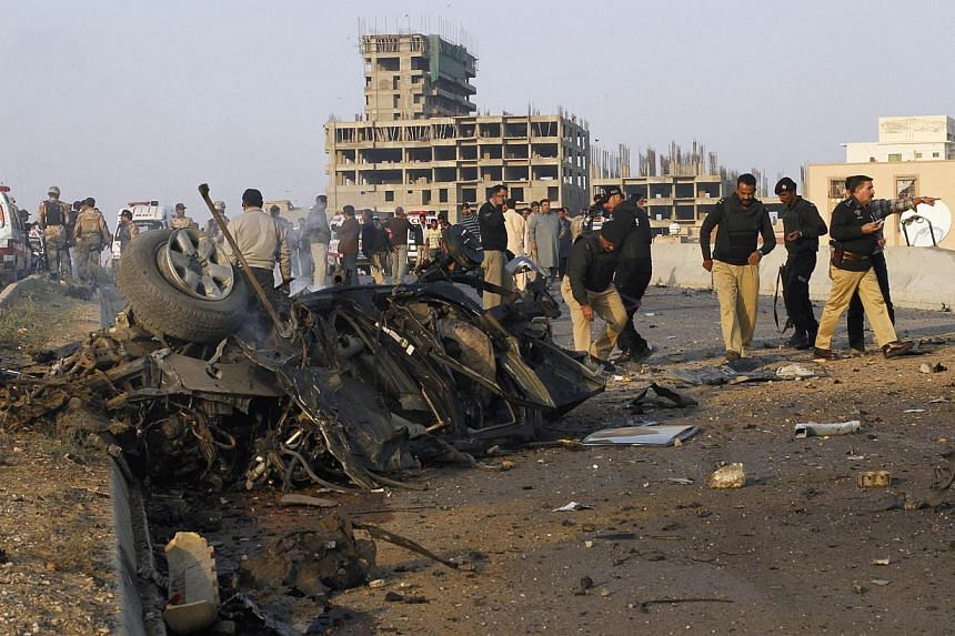 Police collect evidence near the site of a vehicle bomb attack in Karachi, on Jan 9, 2014.Bangladesh police said Monday they have arrested three suspected Pakistani militants who were allegedly carrying a bomb-making manual and other material i