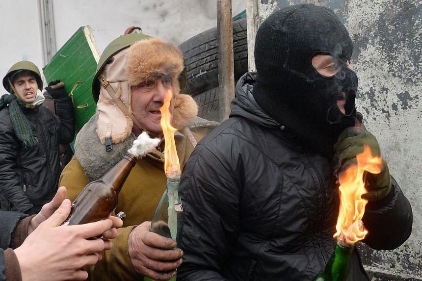 Protesters hold Molotov cocktails during clashes with the police in the centre of Kiev on Jan 20, 2014.Opposition protesters were Monday locked in a tense standoff with Ukrainian police in Kiev after bloody clashes that wounded over 200 people,