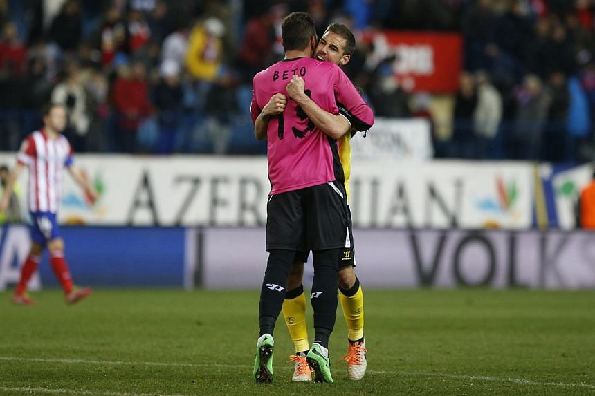 Sevilla's goalkeeper Antonio Alberto Bastos hugs teammate Fernando Navarro at the end of their match against Atletico Madrid at Vicente Calderon stadium in Madrid on Jan 19, 2014. Atletico Madrid missed the chance to move to the top of La Liga after