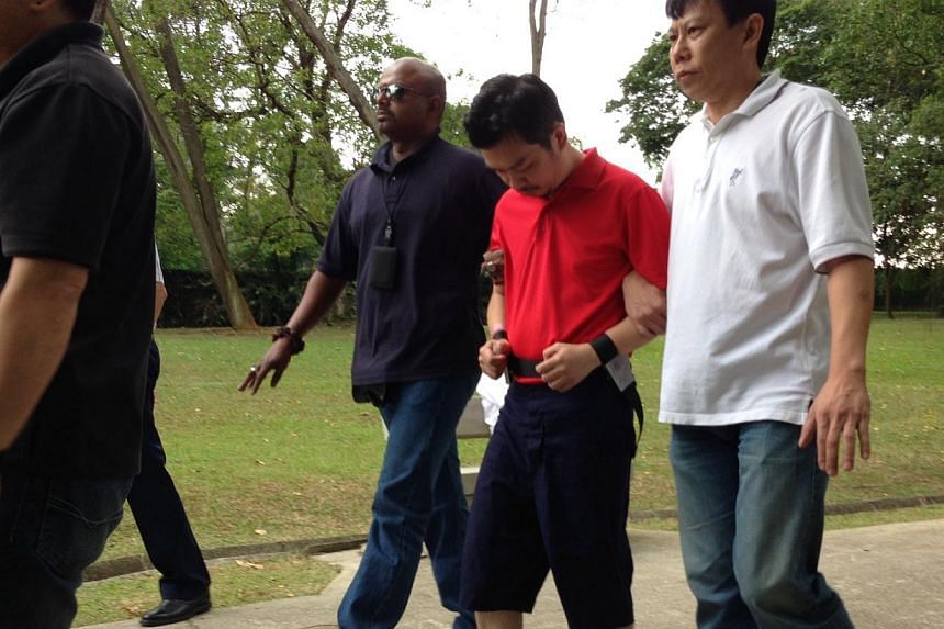 Kidnap suspect Lee Sze Yong, 41 (in red), being escorted by police officers at Sembawang Park on Monday, Jan 20, 2014. Police on Monday afternoon took one of the two Sheng Siong kidnap suspects back to one of the scenes of crime - Sembawang Park. &nb