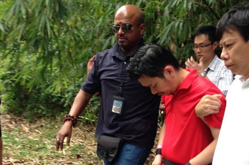 Kidnap suspect Lee Sze Yong (in red) being escorted by police officers at Sembawang Park on Monday, Jan 20, 2014. -- ST PHOTO: YEO SAM JO
