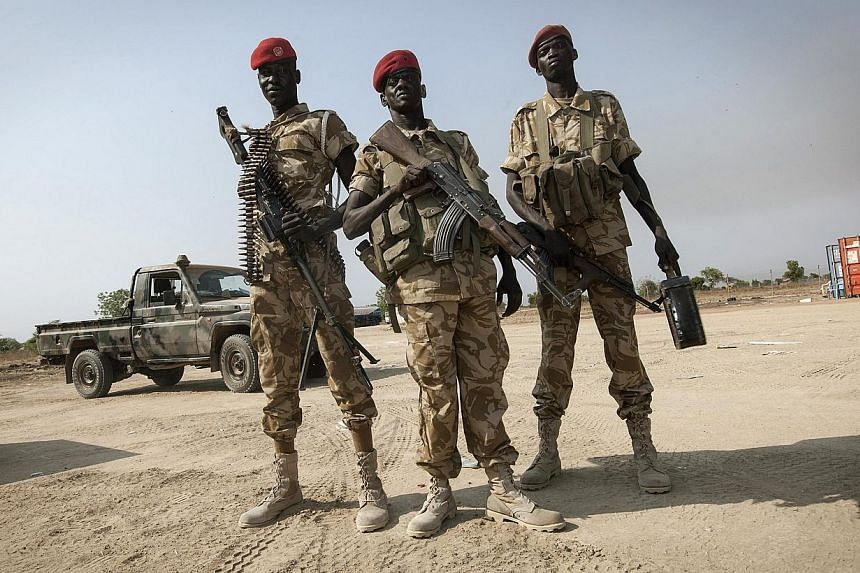 SPLA soldiers stand near a helicopter after returning from a visit to Bor, in Juba on Jan 19, 2014.South Sudanese troops fought on Sunday, Jan 20, 2014, to win back the key oil town of Malakal from rebels loyal to sacked vice-president Riek Mac