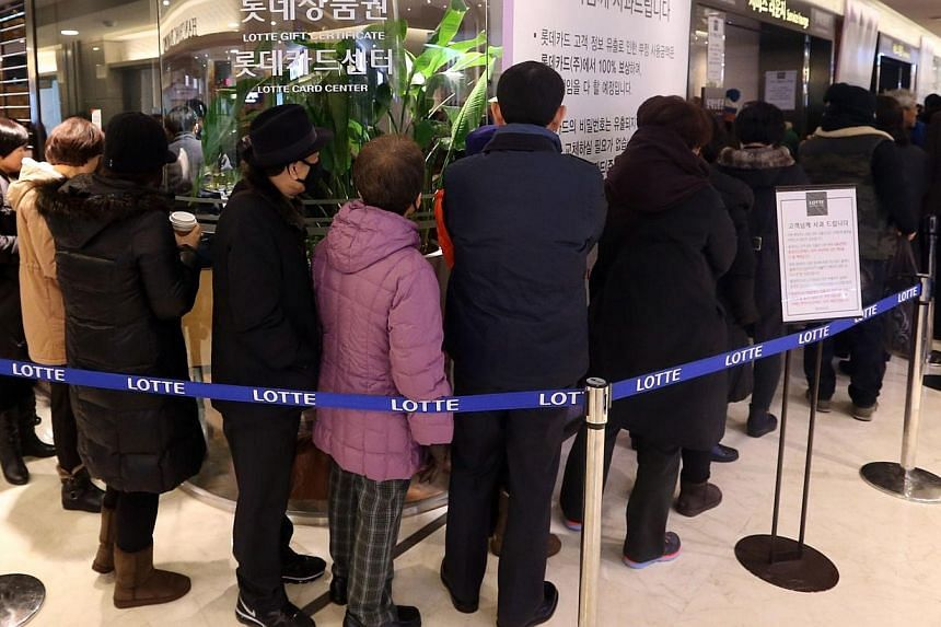 South Korean customers wait in a line to reissue their credit cards at a branch of Lotte Card in Seoul on Tuesday, Jan21, 2014.Tens of thousands of South Koreans flooded banks and call centres on Tuesday to cancel credit cards following t