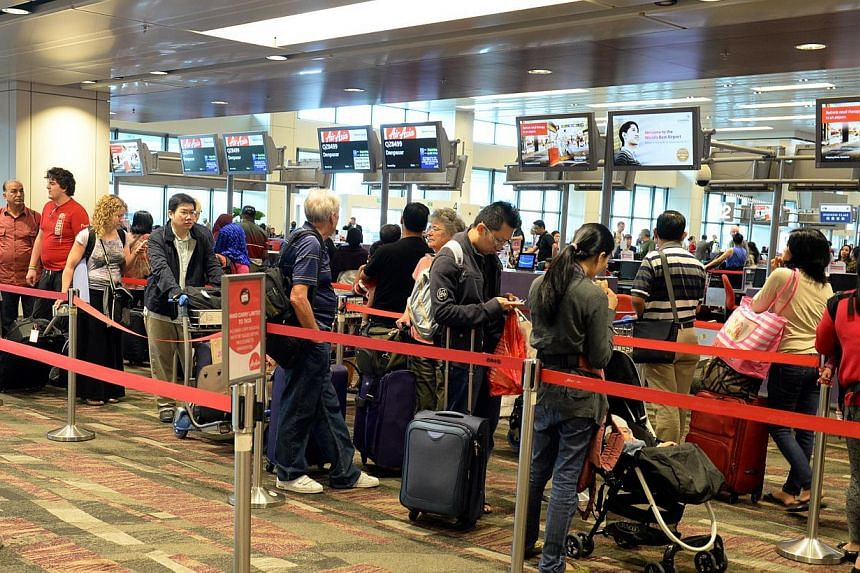 Passengers waiting to check in at the AirAsia counter at Changi Airport Terminal 1. Budget carriers say it is not fair to expect them to meet the same standards as full-service airlines.