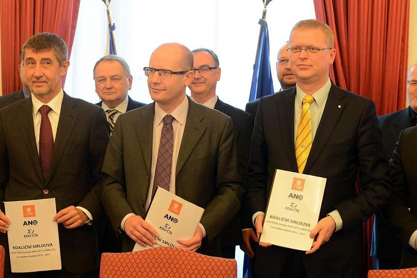 Czech Social Democrats Party (CSSD) leader Bohuslav Sobotka (centre), Christian Democrat party (KDU-CSL) chairman Pavel Belobradek (right) and Czech entrepreneur and leader of the ANO party Andrej Babis pose for the media after signing a coalition ag