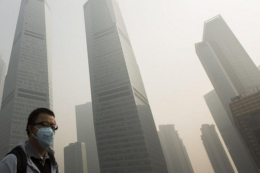 A man wears a mask while walking on a bridge during a hazy day in Shanghai's financial district of Pudong on Dec 5, 2013. Air pollution from China blows across the Pacific Ocean and ends up over the United States west coast - and American consumerism