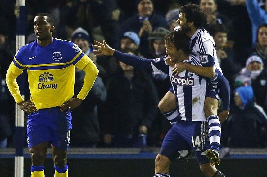 West Bromwich Albion's Diego Lugano (bottom, left) celebrates his goal against Everton with Claudio Yacob during their English Premier League soccer match at The Hawthorns in West Bromwich, central England on Jan 20, 2014. -- PHOTO: REUTERS