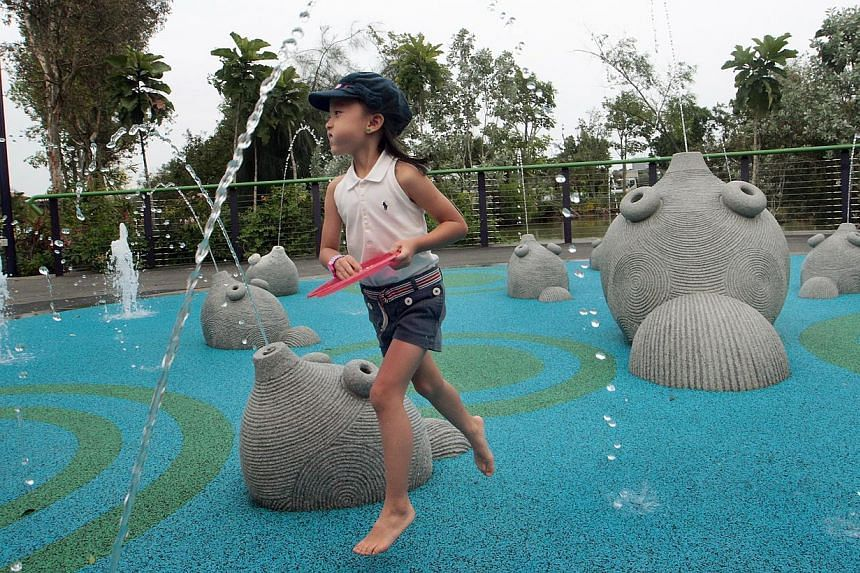 Six-year-old Dana Joy Sim runs away from the Fish Fountain, a toddler water play that offers interactive water play where 17 fish sculptures of varying sizes provide the illusion of fish swimming within the play surface. Families now have anothe