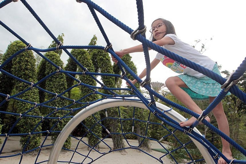 Eight-year-old Sarah Tan climbs on the arch net tunnel, one of the many play structures strung along the Adventure Trail that encourage a variety of motor skills such as jumping, crossing, reaching up and over, and manoeuvring under a low branch.&nbs