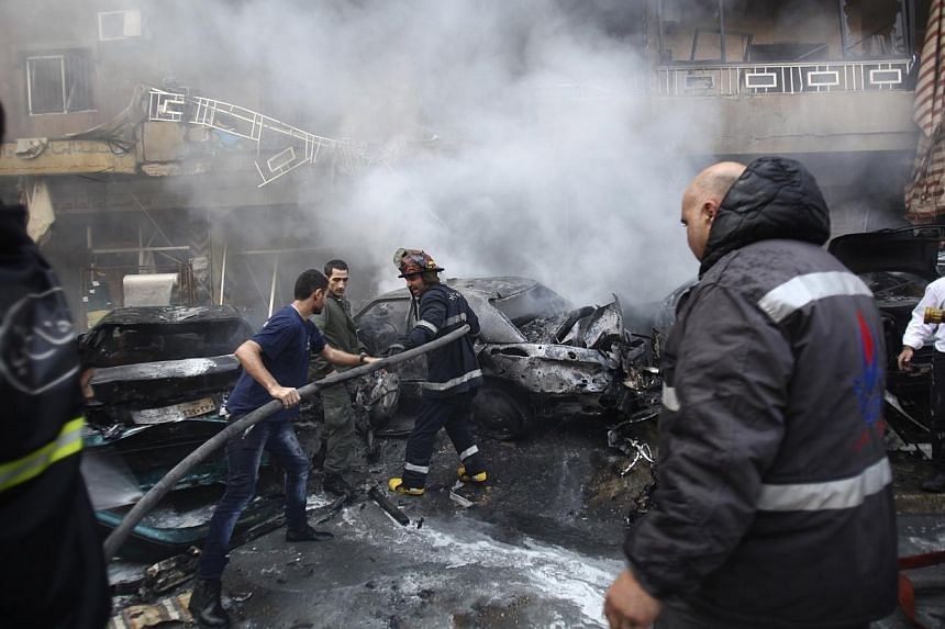 Firefighters extinguish a fire at the site of an explosion in the Haret Hreik area, in the southern suburbs of the Lebanese capital Beirut, on Jan 21, 2014. Two people were killed in a suicide car bombing in a south Beirut neighbourhood considered a