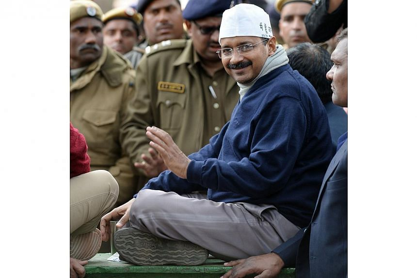 New Delhi Chief Minister Arvind Kejriwal smiles as he sits during a protest in the streets of New Delhi, on Jan 20, 2014. Delhi chief minister Arvind Kejriwal on Tuesday, Jan 21, 2014, called off his sit-in protest to demand police reforms that has s