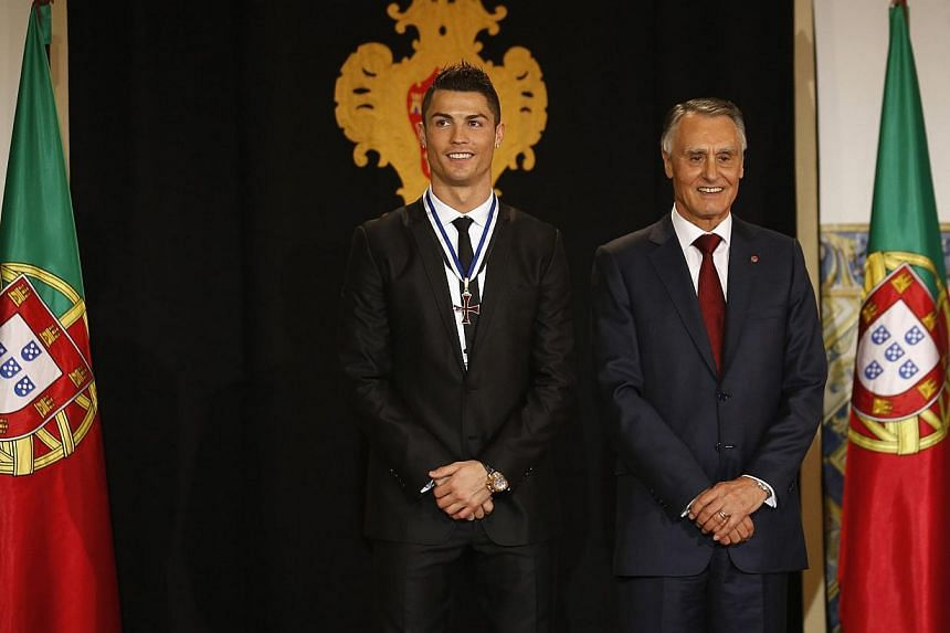 Portugal's soccer team captain Cristiano Ronaldo poses with Portugal's President Anibal Cavaco Silva (right) after receiving the Ordem do Infante Dom Henrique in Lisbon onJan 20, 2014.-- PHOTO: REUTERS