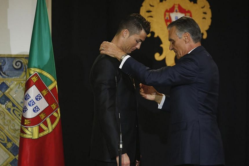 Portugal's soccer team captain Cristiano Ronaldo is decorated with the Ordem do Infante Dom Henrique by Portugal's President Anibal Cavaco Silva (right) in Lisbon on Jan 20, 2014. -- PHOTO: REUTERS