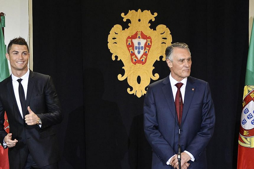 Portuguese forward Cristiano Ronaldo (left) gestures as he poses after being awarded by Portuguese President Anibal Cavaco Silva with the grade of Grand Officer of the Order of Prince Henry the Navigator during a ceremony held at Belem Palace on Jan