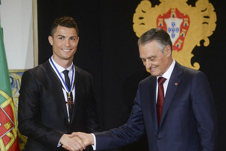 Portuguese forward Cristiano Ronaldo (left) shakes hands with Portuguese President Anibal Cavaco Silva with the grade of Grand Officer of the Order of Prince Henry the Navigator during a ceremony held at Belem Palace on Jan 20, 2014. The Portuguese P