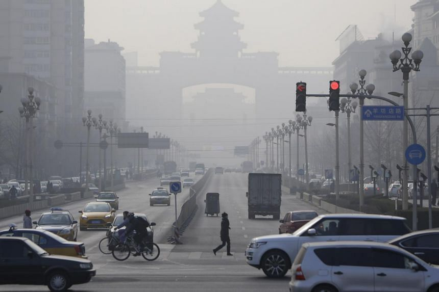 Pedestrians cross the road near the Beijing West Railway Station (background) on a hazy day in Beijing, Jan 17, 2014. Pollution from China travels in large quantities across the Pacific Ocean to the United States, a new study has found, making e