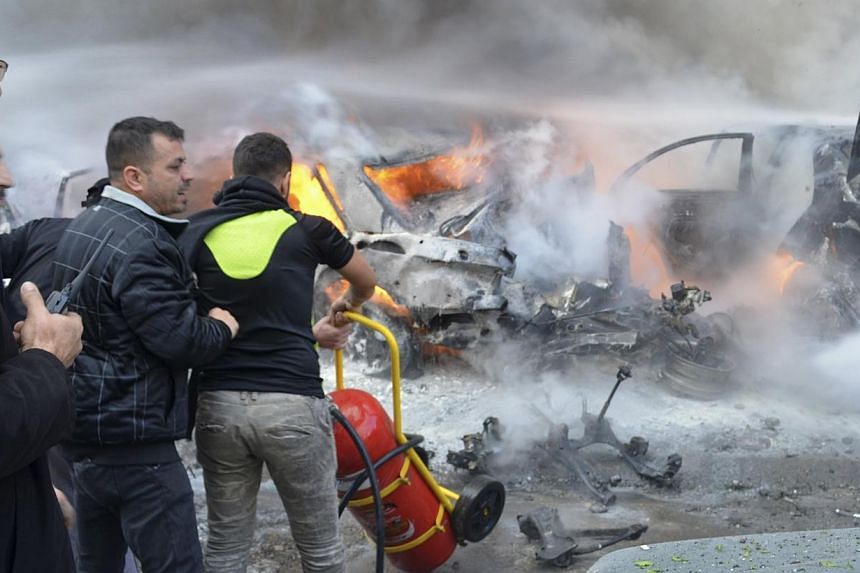 Civil Defence members move a fire extinguisher as a Hizbollah member carries a walkie-talkie at the site of an explosion in the Haret Hreik area, in the southern suburbs of the Lebanese capital Beirut. Four people were killed in an apparent suicide c